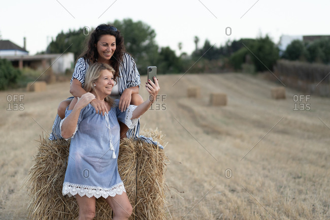 Company of mature women in summer outfit gathering at haystack and taking photo on cellphone while enjoying weekend in countryside together