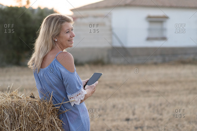 Smiling female standing in dried field and taking photo on smartphone on background of scenic sundown in rural area