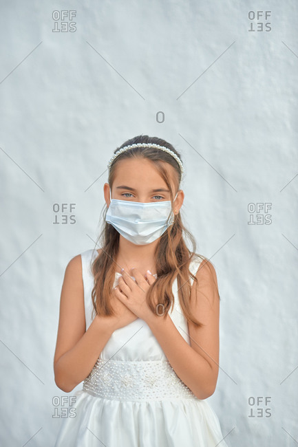 Preteen blond girl in a white dress wearing a protective mask because of the covid-19 pandemic, on the day of her first communion standing on white wall background