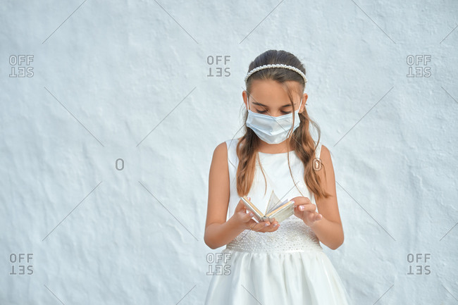 Preteen blond girl in a white dress wearing a protective mask because of the covid-19 pandemic, on the day of her first communion standing outside a church holding a notebook