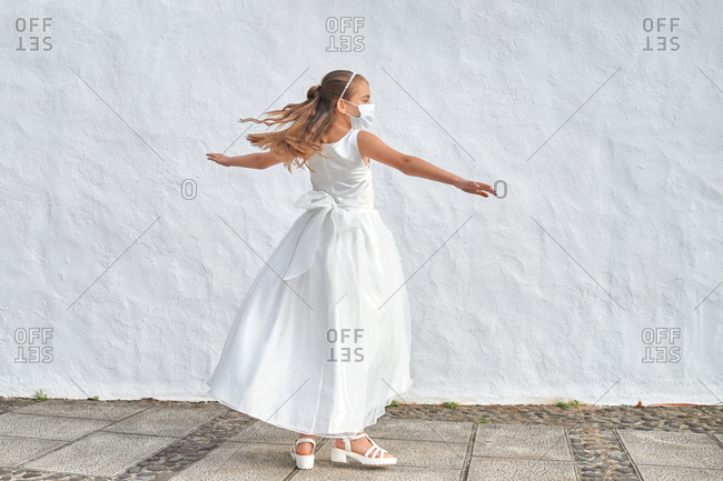 Preteen blond girl in a white dress wearing a protective mask because of the covid-19 pandemic, on the day of her first communion dancing outside a church