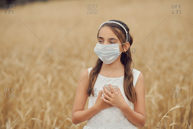 Preteen blond girl in a white dress wearing a protective mask because of the covid-19 pandemic, on the day of her first communion standing looking away in the middle of a golden meadow