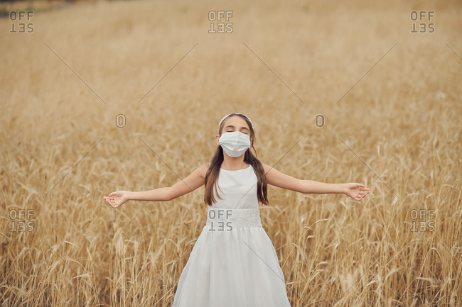 Preteen blond girl in a white dress wearing a protective mask because of the covid-19 pandemic, on the day of her first communion standing with eyes closed and open arms in the middle of a golden meadow