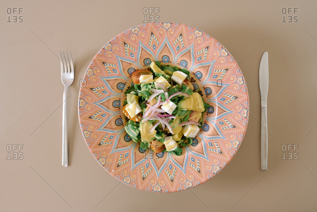 From above of tasty Italian salad with fresh mozzarella cubes and basil leaves near tomatoes and thin slices of red onion decorated with mustard sauce in ceramic plate near cutlery