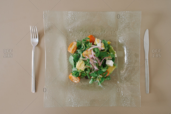 From above of tasty salad with fresh mozzarella cubes, tomatoes and thin slices of red onion decorated with mustard sauce in a glass crystal clear plate near cutlery