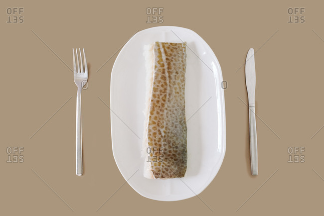 Top view of uncooked fresh fish fillet on white ceramic plate knife and fork on beige background