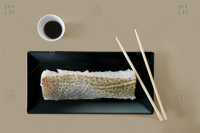 Top view of uncooked fresh fish fillet on black ceramic plate near small bowl with salty soybean sauce and wooden chopsticks on beige background
