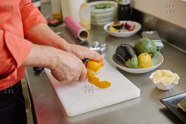 From above of crop anonymous chef using peeler while peeling fresh lemon during cooking process near plate with raw fish and vegetables on metal surface