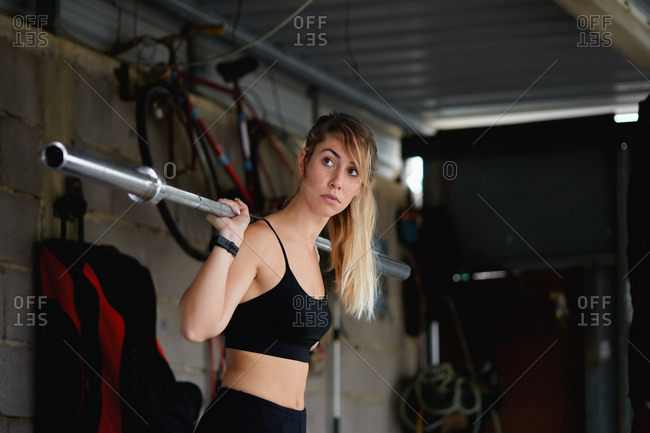 Side view fit concentrated female in black activewear performing exercises using barbell with no weight on shoulders in garage gym