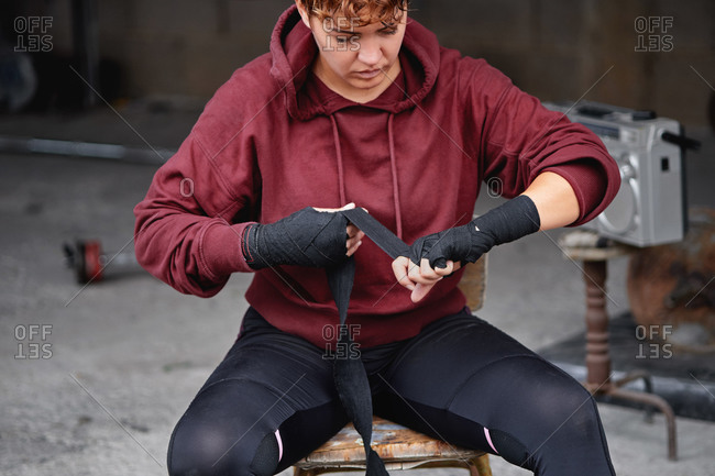 Crop concentrated female boxer in leggings and hoodie wrapping hands with black boxing wraps before boxing workout in shabby basement gym
