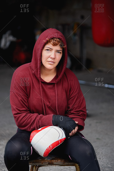Concentrated female boxer in leggings and hoodie wrapping hands with black boxing wraps before boxing workout in shabby basement gym