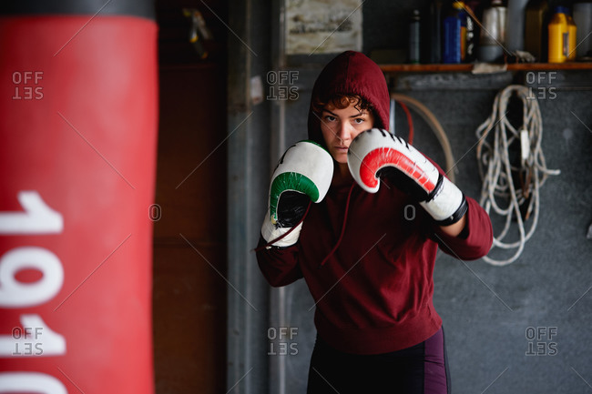 Strong female boxer wearing dark red hoodie and boxing gloves shadows boxing and throwing punches in air while working out in garage gym