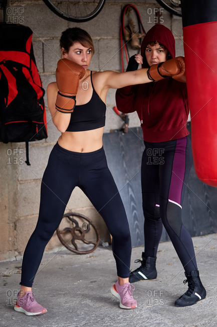 Full body sporty focused female fighters wearing sportswear and boxing gloves hitting punching bag during intense working out together in garage gym