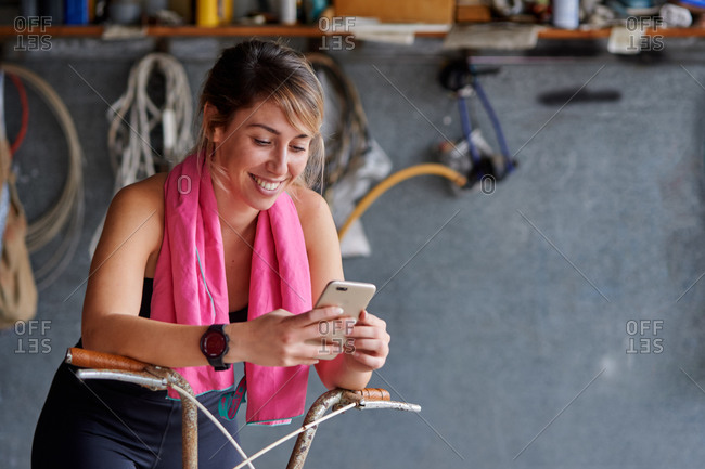 Full body smiling female bicyclist in sportswear sitting on bicycle and browsing mobile phone in messy garage while resting after ride
