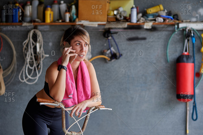 Full body smiling female bicyclist in sportswear sitting on bicycle and talking mobile phone in messy garage while resting after ride