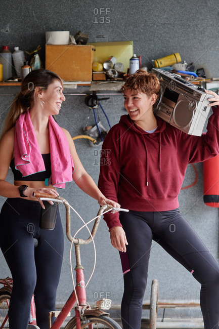 Cheerful fit sportswomen with old fashioned tape player resting on cycle and chatting after intense workout in garage gym