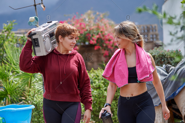 Happy young sportswomen in activewear with towel and reusable water bottle carrying old fashioned tape player on shoulder while walking together in sunny country house backyard after workout