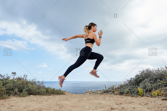 Side view full body slim determined female runner in black leggings and sports bra jogging and jumping on seashore against calm blue sea during sunny day