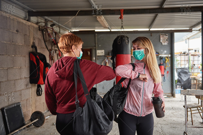 Sporty females in activewear with sports bags and protective face masks greeting each other with elbow bumps in rural garage gym during coronavirus outbreak
