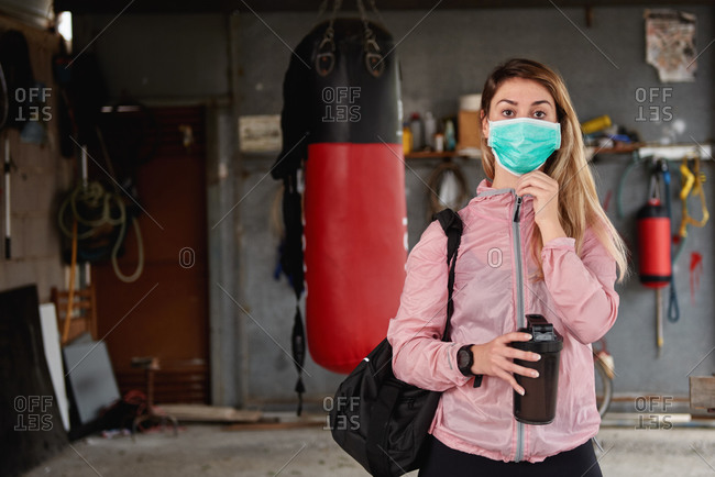 Serious fit sportswoman with sports bag and reusable water bottle wearing medical mask before leaving garage gym during coronavirus epidemic and looking at camera