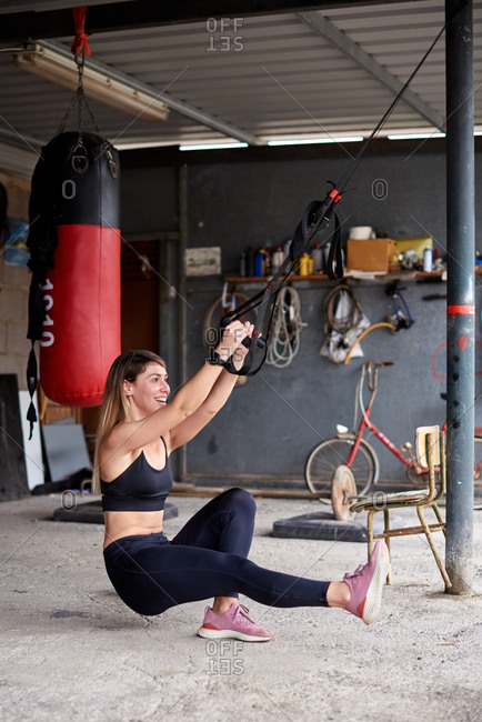 Side view full length cheerful fit female in sportswear performing single leg squats for butt legs with suspension straps in rural garage gym
