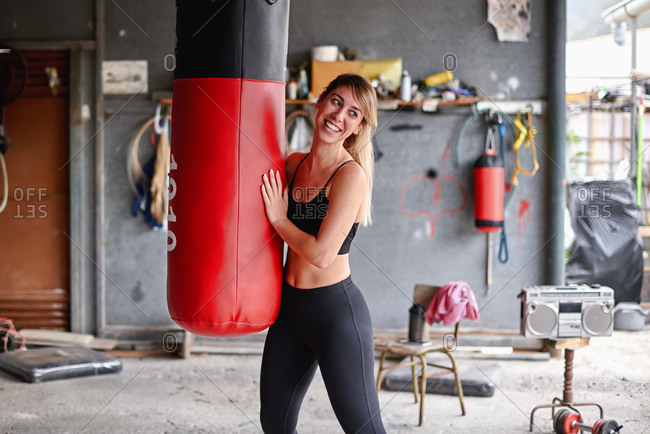 Positive young sportswoman wearing leggings and sports bra hugging punching bag and looking away happily after intense workout in messy rural garage gym