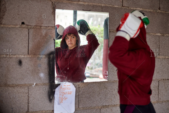 Serious sportswoman wearing hoodie and boxing gloves standing in double biceps pose and looking in mirror on rural shabby wall