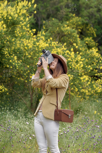 Female photographer in hat with closed eyes filming video with retro video camera while standing near trees with blooming yellow flowers in daylight