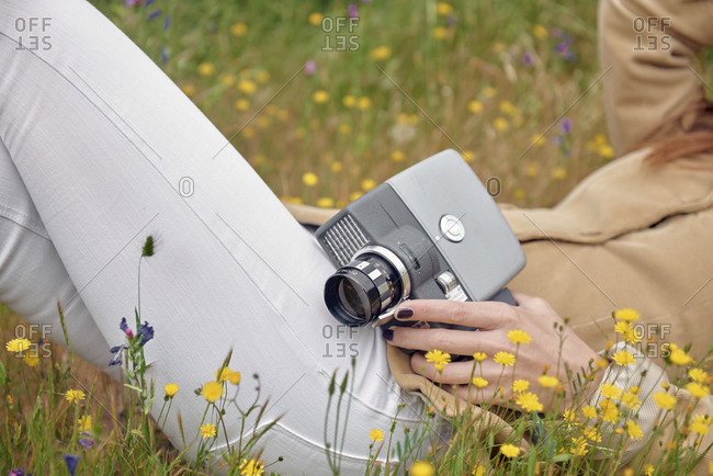 Side view of slender anonymous female photographer in jeans covering face with hat while lying on meadow with colorful flowers and holding old video camera in countryside