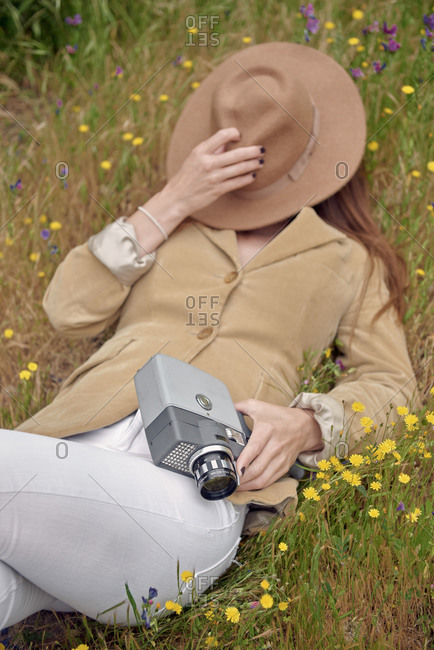 From above of slender anonymous female photographer in jeans covering face with hat while lying on meadow with colorful flowers and holding old video camera in countryside
