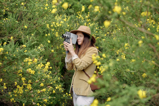 Smiling slim woman in casual wear and hat strolling with old video camera and leather case near bushes with colorful blooming flowers in countryside and looking away
