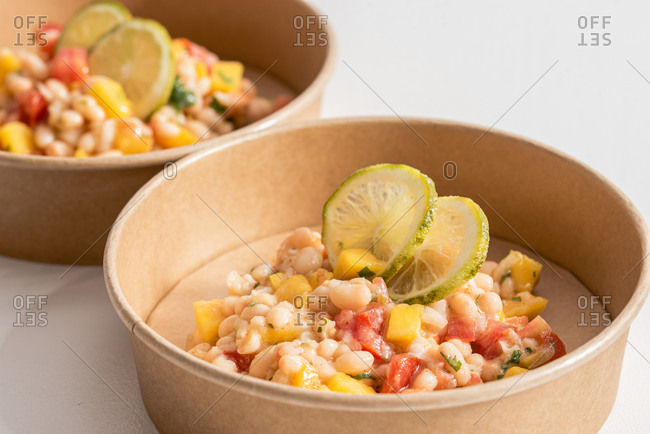 Closeup of palatable Prawn Ceviche with beans and tomatoes garnished with lime slices and placed in takeaway eco friendly bowls
