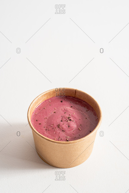 From above of yummy beetroot cream in eco friendly cardboard bowl placed on white table