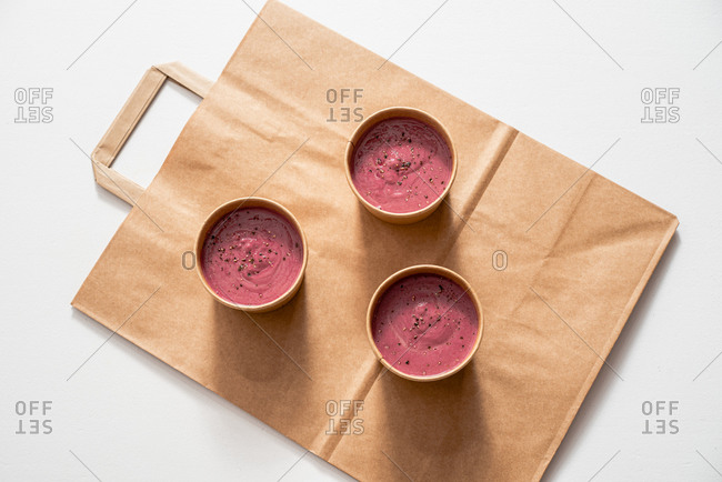 From above of yummy beetroot cream in eco friendly cardboard bowls placed on craft takeaway bag on white table