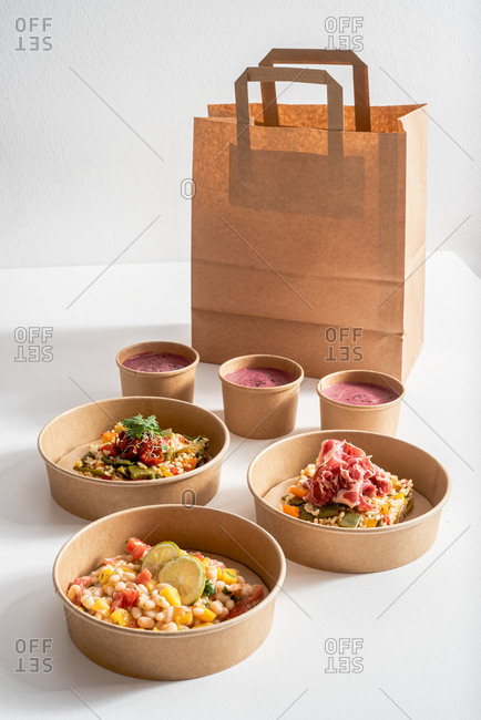 From above Molí de Pals vegetable rice, iberico ham and Shrimp Ceviche in carton bowls placed on paper bag on table with delicious beetroot cream