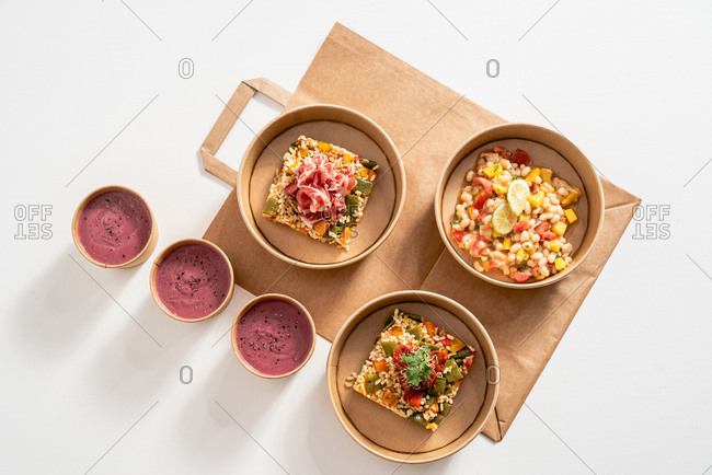 Top view of rice with vegetables Molí de Pals and Molí de Pals rice and Shrimp Ceviche in carton bowls placed on paper bag on table with delicious beetroot cream