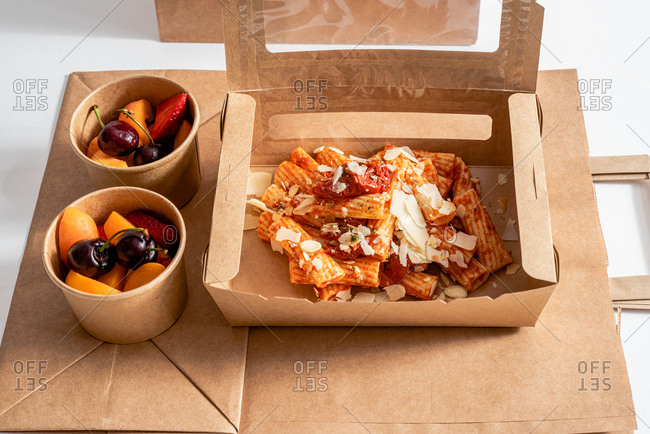 High angle of delicious pasta with pesto sauce placed in carton boxes to go and placed on table with fresh fruits in bowls