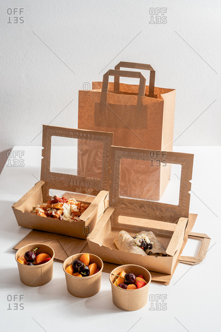 High angle of delicious pasta with pesto sauce and buckwheat crepe with roasted vegetables placed in carton boxes to go and placed on table with fresh fruits in bowls