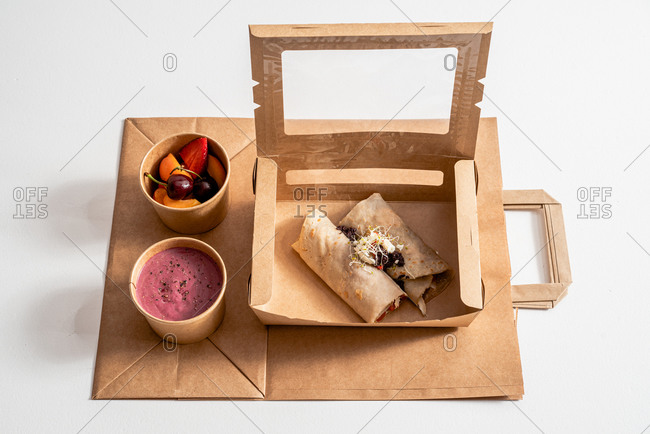 From above of delicious buckwheat crepe with roasted vegetables in carton container arranged with beetroot cream and ripe fruits in bowls on table
