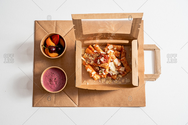 High angle of delicious pasta with pesto sauce and beetroot cream placed in carton boxes to go and placed on table with fresh fruits in bowls