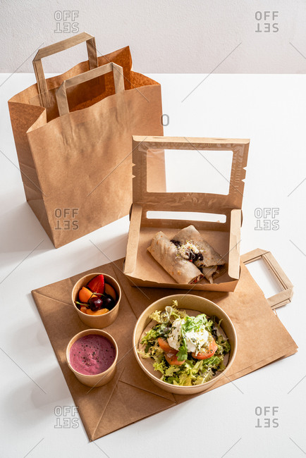 From above of delicious buckwheat crepe with roasted vegetables in carton container arranged with mozzarella cheese salad and beetroot cream and ripe fruits in bowls on table