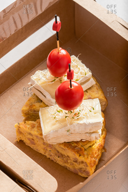 High angle closeup of delicious omelette garnished with cheese and cherry tomatoes and placed in eco friendly cardboard box