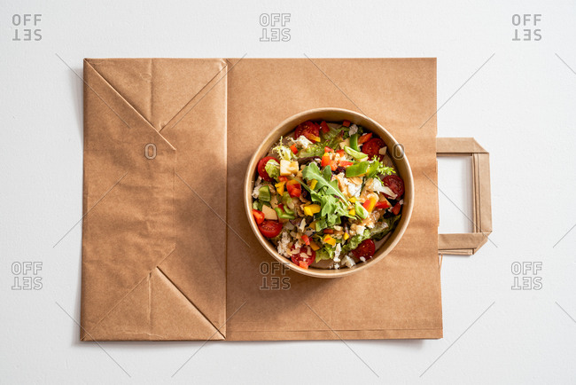 Top view of palatable vegetable salad with various nutritious ingredients in cardboard bowl placed on paper bag