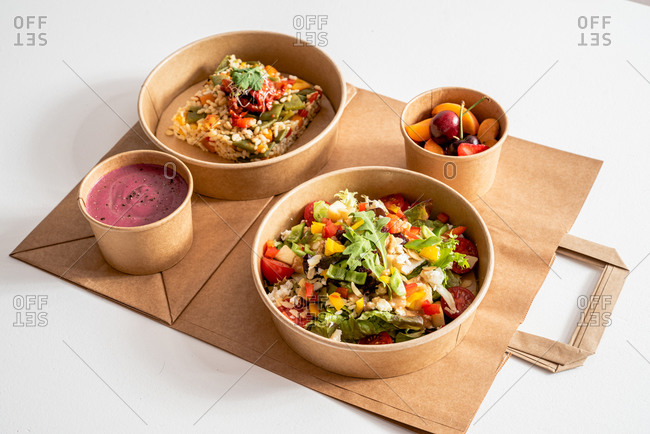 Top view of palatable vegetable salad with various nutritious ingredients in cardboard bowl placed on paper bag near rice with Molí de Pals vegetable rice and beetroot cream and fruit bowl