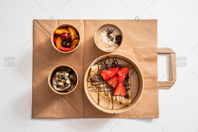 Top view of various ice creams decorated with chocolate and almond petals near assorted fresh fruits and buckwheat crepe with strawberry slices in eco friendly boxes on takeaway bag