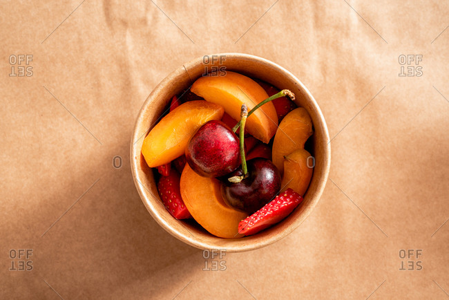 Top view of ripe strawberry and peach slices mixed with bright cherries in round takeaway organic cardboard box on parchment