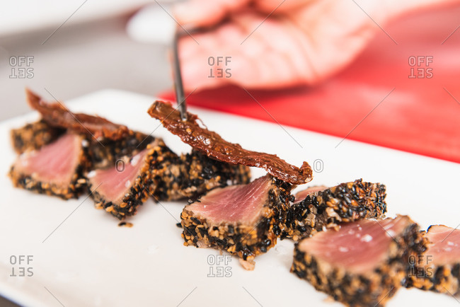 Close up of cropped unrecognizable person dressing up tuna tataki plate