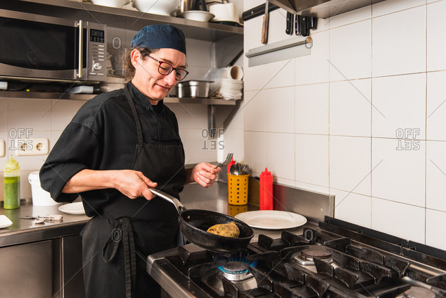 Female cook working with a frying pan on a restaurant kitchen