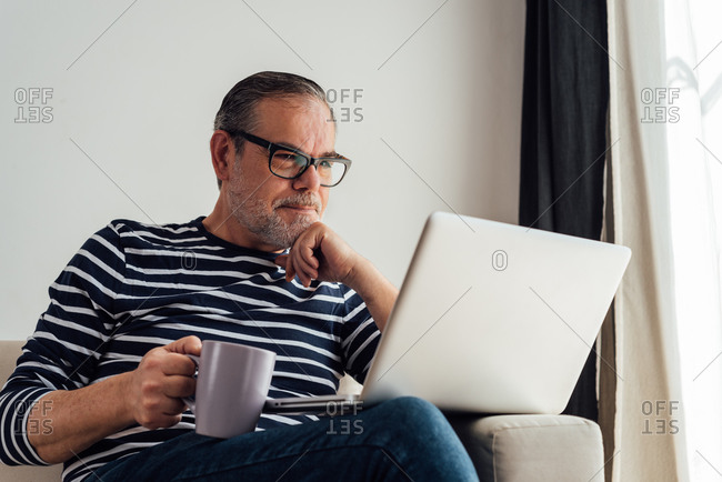 Focused male in glasses drinking coffee and surfing laptop while working at home because of quarantine