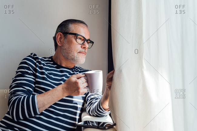 Side view of bearded man looking out of a windows while enjoying hot beverage in morning at home